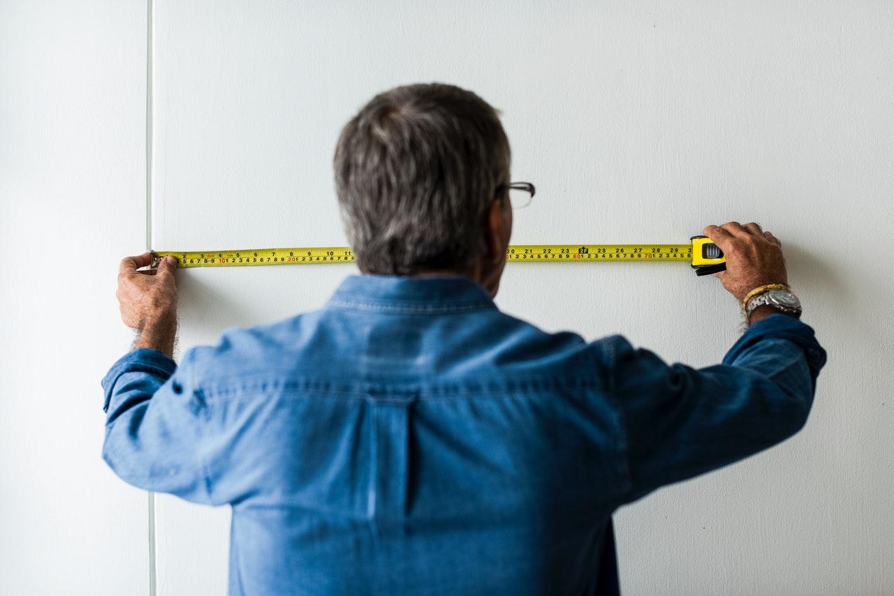 Budowlaniec mierzący ścianę