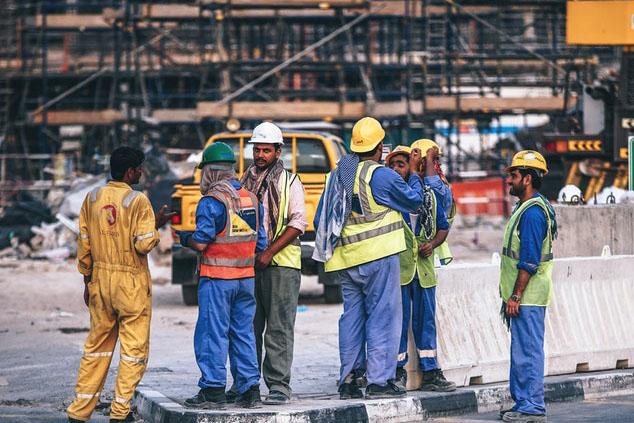 Pracownicy budowlani na tle rusztowania
