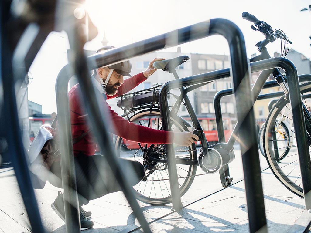 Mężczyzna pdpina rower do stojaka rowerowego
