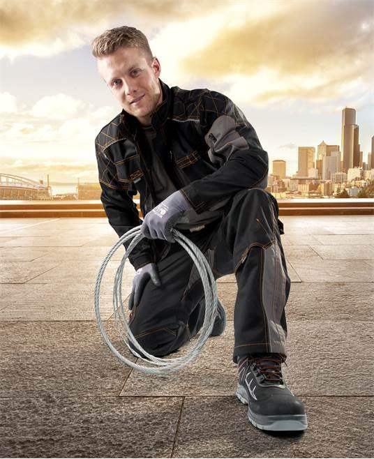 mężczyzna w roboczym ubraniu w drutem w dłoni