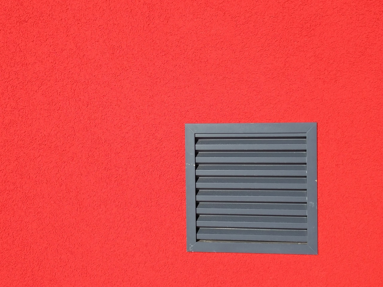 Czerwona ściana z czarną kratką wentylacyjną, z której wieje